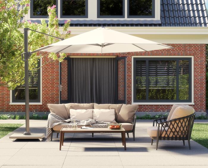 Challenger parasol (wit) in een tuin met een grijze bank, tafel en stoel.